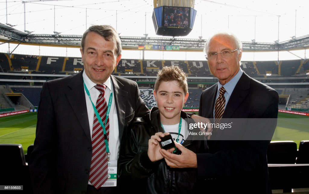 Nick Moor is surrounded by DFB General Secretary Wolfgang Niersbach and Franz Beckenbauer as he presents his DFB soccer award before the Women's...