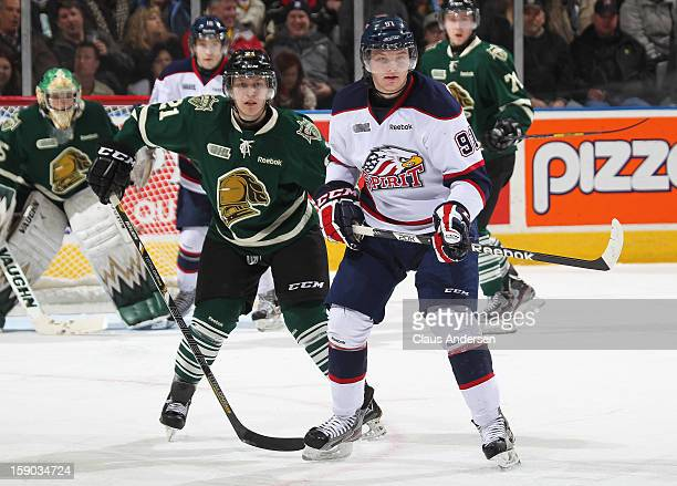Nick Moutrey of the Saginaw Spirit is held in check by Tyler Ferry of the London Knights in an OHL game on January 4 2013 at the Budweiser Gardens in...