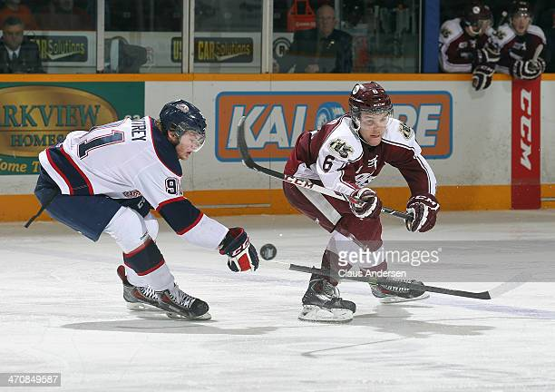 Nick Moutrey of the Saginaw Spirit tries to stop a clearing attempt by Brandon Devlin of the Peterborough Petes during an OHL game at the Memorial...