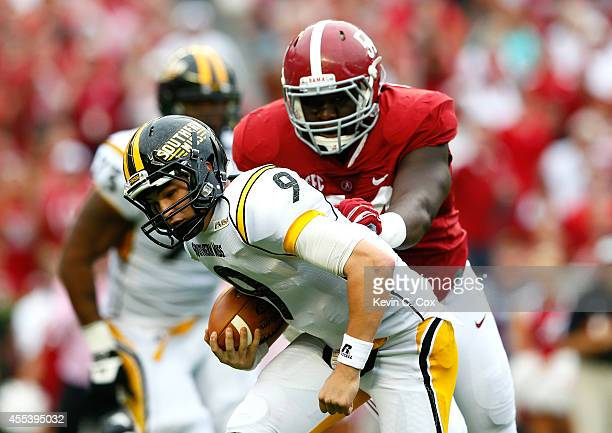 Nick Mullens of the Southern Miss Golden Eagles rushes away from Dalvin Tomlinson of the Alabama Crimson Tide at BryantDenny Stadium on September 13...