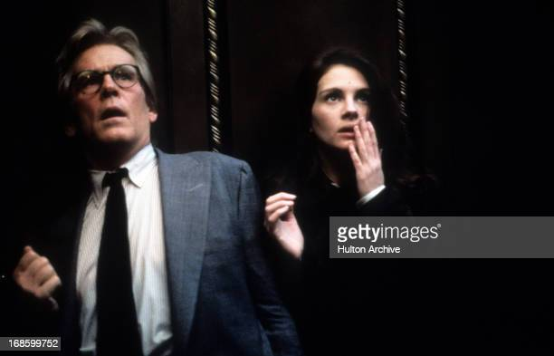 Nick Nolte and Julia Roberts standing next to each other in shock of something they see in front of them in a scene from the film 'I Love Trouble'...