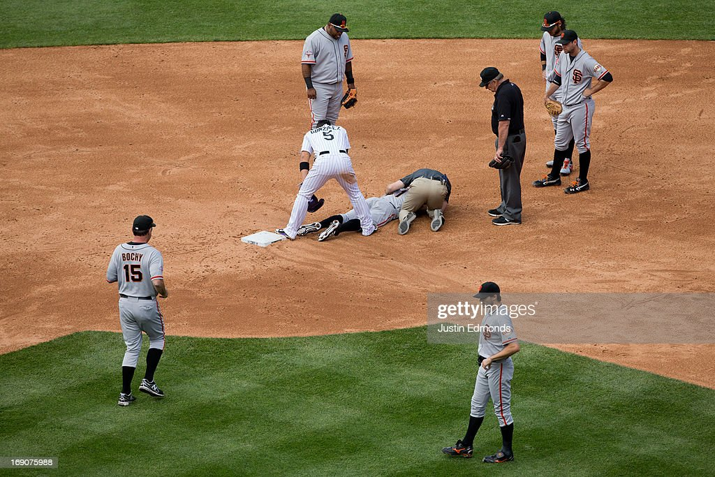 Nick Noonan #21 of the San Francisco Giants gets attended to by the training staff after being knocked to the ground by Carlos Gonzalez #5 of the Colorado Rockies on a pickoff attempt as Manager <a gi-track='captionPersonalityLinkClicked' href=/galleries/search?phrase=Bruce+Bochy&family=editorial&specificpeople=220291 ng-click='$event.stopPropagation()'>Bruce Bochy</a> #15, <a gi-track='captionPersonalityLinkClicked' href=/galleries/search?phrase=Barry+Zito&family=editorial&specificpeople=202943 ng-click='$event.stopPropagation()'>Barry Zito</a> #75, <a gi-track='captionPersonalityLinkClicked' href=/galleries/search?phrase=Pablo+Sandoval&family=editorial&specificpeople=803207 ng-click='$event.stopPropagation()'>Pablo Sandoval</a> #48, <a gi-track='captionPersonalityLinkClicked' href=/galleries/search?phrase=Brandon+Crawford&family=editorial&specificpeople=5580312 ng-click='$event.stopPropagation()'>Brandon Crawford</a> #35, <a gi-track='captionPersonalityLinkClicked' href=/galleries/search?phrase=Brandon+Belt&family=editorial&specificpeople=7513394 ng-click='$event.stopPropagation()'>Brandon Belt</a> #9 and second base umpire Bob Davidson look on during the third inning at Coors Field on May 19, 2013 in Denver, Colorado. The Rockies defeated the Giants 5-0.