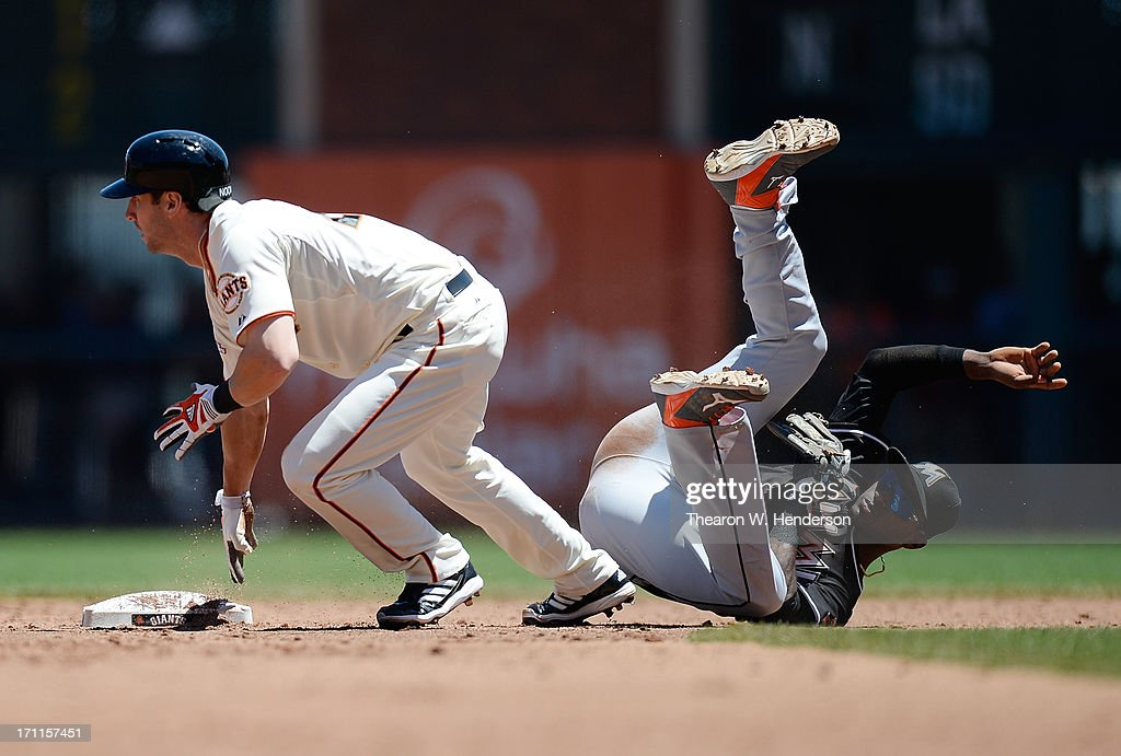 Nick Noonan #21 of the San Francisco Giants gets back to second base safe as the ball is thrown into centerfield past Adeiny Hechavarria #3 of the Miami Marlins in the third inning at AT&T Park on June 22, 2013 in San Francisco, California.