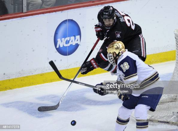 Nick Oliver of the St Cloud State Huskies and TJ Tynan of the Notre Dame Fighting Irish skate after the puck during the third period of the West...
