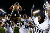 Nick Padla Donavon Clark and Jermaine Edmondson of the Michigan State Spartans celebrate with the paul bunyan trophy after defeating the Michigan...