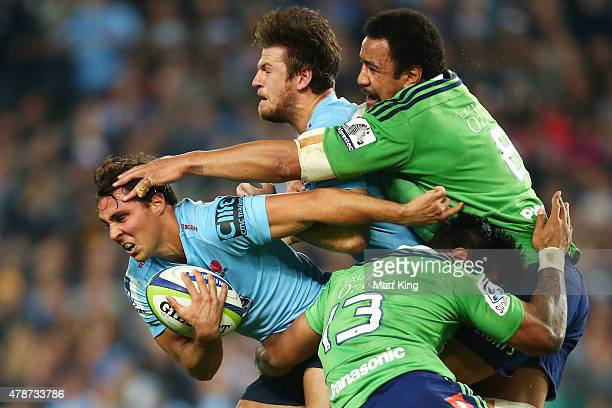 Nick Phipps of the Waratahs is tackled by Malakai Fekitoa and Nasi Manu of the Highlanders with Rob Horne of the Waratahs in support during the Super...