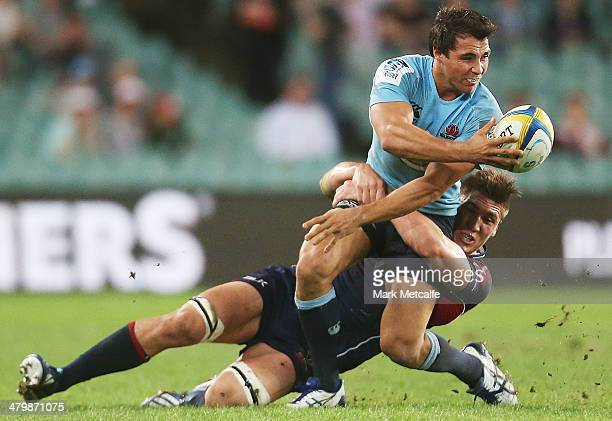 Nick Phipps of the Waratahs passes as he is tackled during the round six Super Rugby match between the Waratahs and the Rebels at Allianz Stadium on...