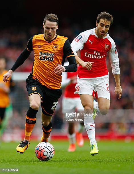 Nick Powell of Hull City runs with the ball next to Mathieu Flamini of Arsenal during the Emirates FA Cup fifth round match between Arsenal and Hull...