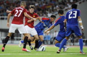 Nick Powell of Manchester United challenges with Wang Shouting of Shanghai Shenhua during the Friendly Match between Shanghai Shenhua and Manchester...