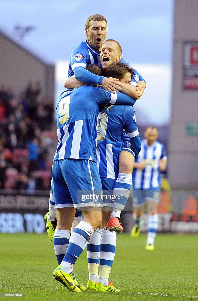 Nick Powell (R) of Wigan Athletic celebrates with team-mates <a gi-track='captionPersonalityLinkClicked' href=/galleries/search?phrase=Grant+Holt&family=editorial&specificpeople=2091078 ng-click='$event.stopPropagation()'>Grant Holt</a> (L) <a gi-track='captionPersonalityLinkClicked' href=/galleries/search?phrase=Ben+Watson+-+Fu%C3%9Fballspieler&family=editorial&specificpeople=15154828 ng-click='$event.stopPropagation()'>Ben Watson</a> (Top centre) and James McArthur (Top left) after he scores the second goal of the game for his side during the Sky Bet Championship match between Wigan Athletic and Bolton Wanderers at the DW Stadium on December 15, 2013 in Wigan, England.