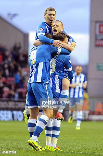 Nick Powell of Wigan Athletic celebrates with teammates Grant Holt Ben Watson and James McArthur after he scores the second goal of the game for his...