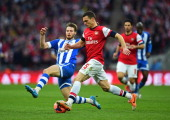 Nick Powell of Wigan Athletic challenges Thomas Vermaelen of Arsenal during the FA Cup SemiFinal match between Wigan Athletic and Arsenal at Wembley...