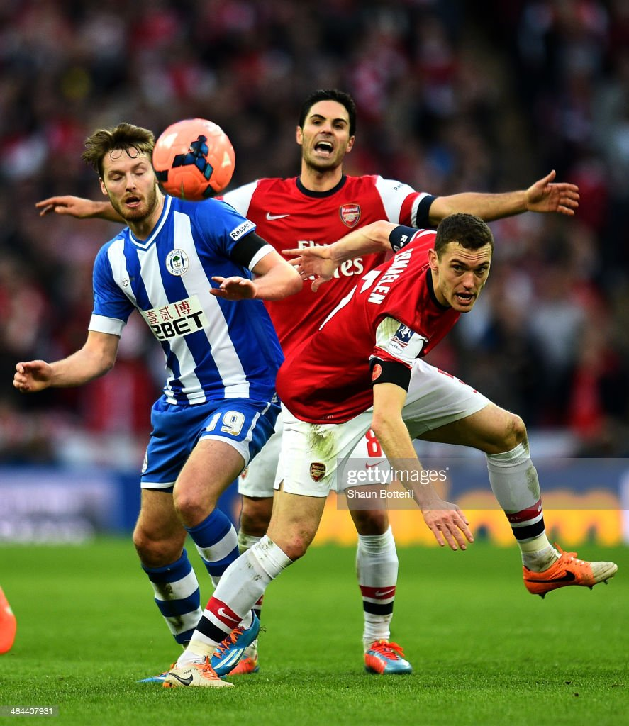 Nick Powell of Wigan Athletic, <a gi-track='captionPersonalityLinkClicked' href=/galleries/search?phrase=Mikel+Arteta&family=editorial&specificpeople=235322 ng-click='$event.stopPropagation()'>Mikel Arteta</a> and <a gi-track='captionPersonalityLinkClicked' href=/galleries/search?phrase=Thomas+Vermaelen&family=editorial&specificpeople=1360240 ng-click='$event.stopPropagation()'>Thomas Vermaelen</a> of Arsenal compete for the ball during the FA Cup Semi-Final match between Wigan Athletic and Arsenal at Wembley Stadium on April 12, 2014 in London, England.