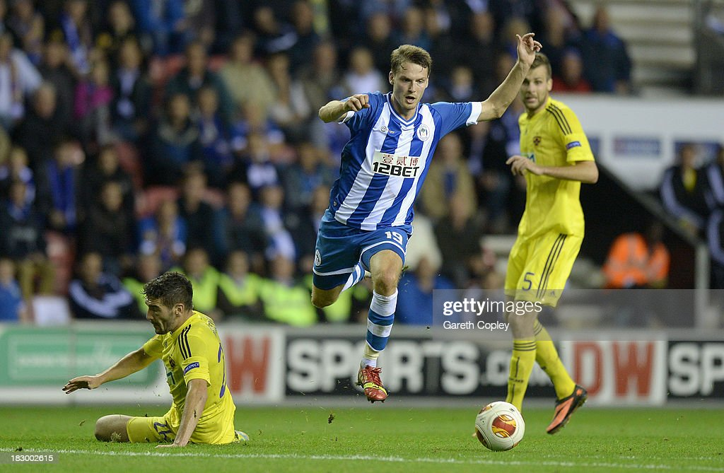 Nick Powell of Wigan gets past Alexsander Rajcevic of NK Maribor on his way to scoring his team's 3rd goal during the UEFA Europa League match between Wigan and NK Maribor at DW Stadium on October 3, 2013 in Wigan, England.