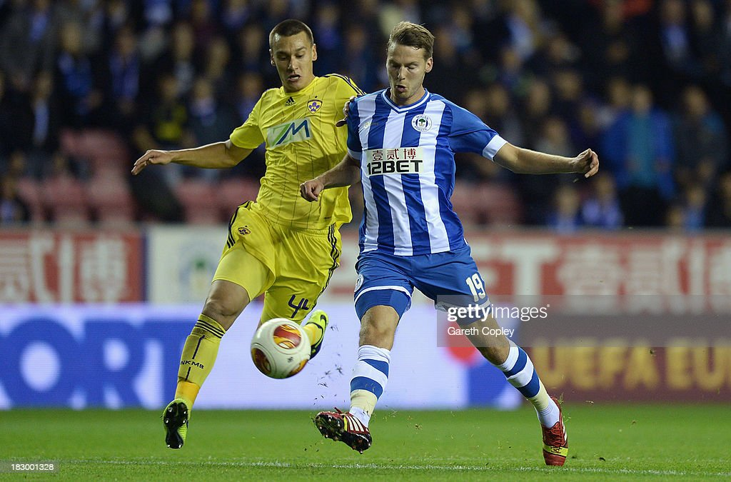 Nick Powell of Wigan is tackled by Arghus of Maribor during the UEFA Europa League match between Wigan and NK Maribor at DW Stadium on October 3, 2013 in Wigan, England.