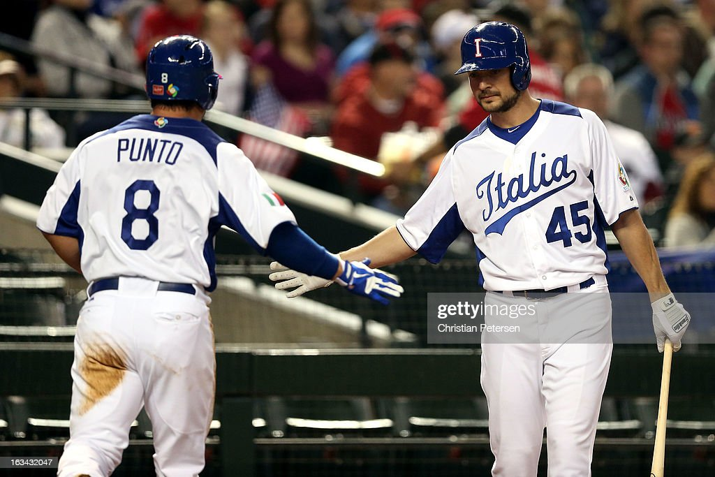 Nick Punto #8 and Mario Chiarini #45 of Team Italy celebrate after scoring a run in the first inning against Ryan Vogelsong #32 of Team USA during the World Baseball Classic First Round Group D game at Chase Field on March 9, 2013 in Phoenix, Arizona.