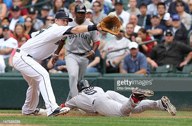 Nick Punto of the Boston Red Sox slides into first on a bunt single as Justin Smoak of the Seattle Mariners takes the throw at Safeco Field on July 1...