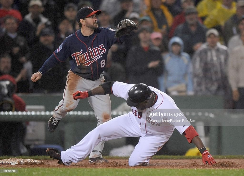 Nick Punto #8 of the Minnesota Twins waits for a throw while David Ortiz #34 of the Boston Red Sox slides safely into third base in the fourth inning on May 19, 2010 at Fenway Park in Boston, Massachusetts. The hit was later reviewed and determined to be a home run.