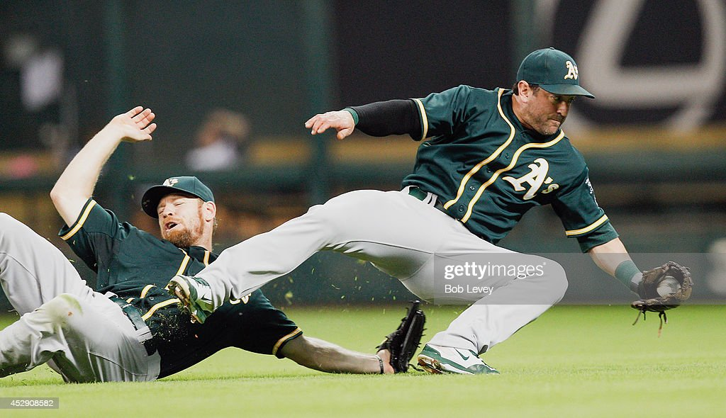 Nick Punto #1 of the Oakland Athletics avoids a collision with Brandon Moss #37 as he makes the final out against the Houston Astros at Minute Maid Park on July 29, 2014 in Houston, Texas.