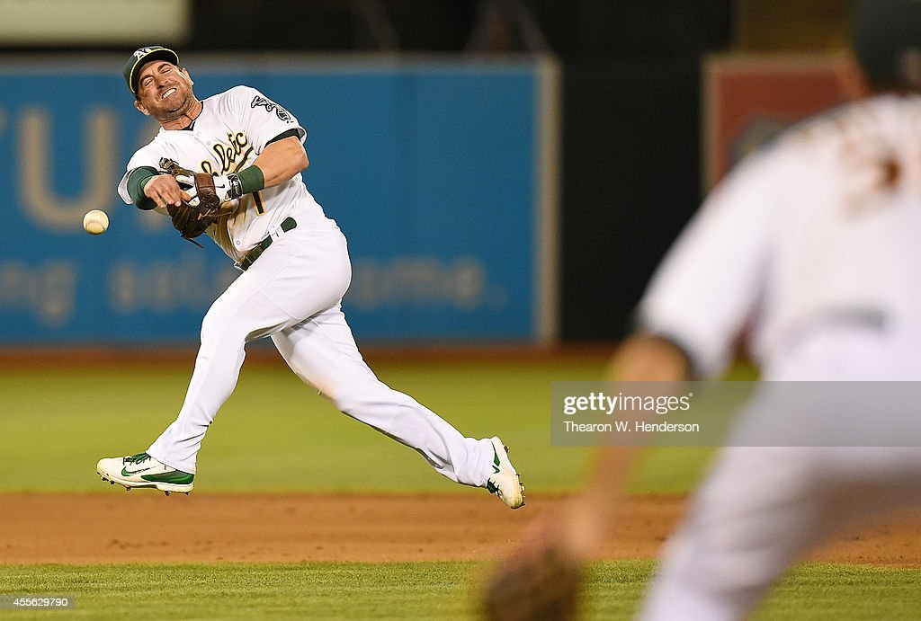 Nick Punto #1 of the Oakland Athletics makes an off-balance throw to first base against Adam Rosales of the Texas Rangers in the top of the fifth inning at O.co Coliseum on September 17, 2014 in Oakland, California. Punto was late with the throw.