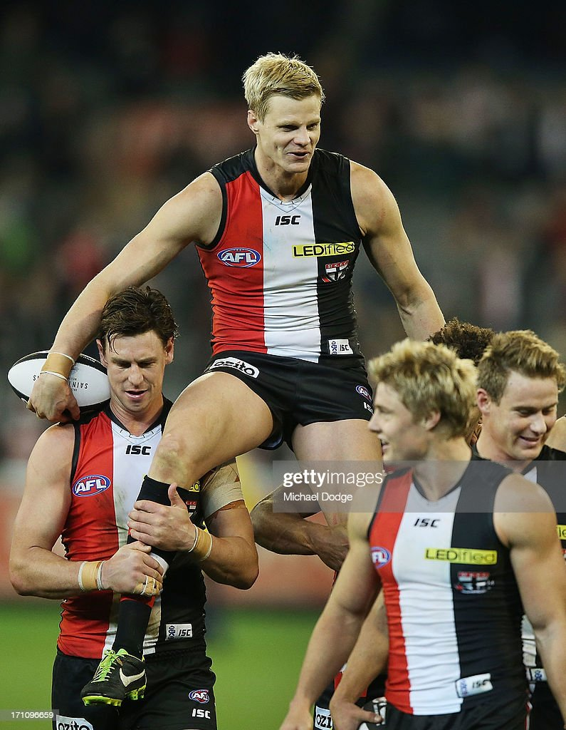 <a gi-track='captionPersonalityLinkClicked' href=/galleries/search?phrase=Nick+Riewoldt&family=editorial&specificpeople=176552 ng-click='$event.stopPropagation()'>Nick Riewoldt</a> gets carried off by <a gi-track='captionPersonalityLinkClicked' href=/galleries/search?phrase=Justin+Koschitzke&family=editorial&specificpeople=220971 ng-click='$event.stopPropagation()'>Justin Koschitzke</a> after his 250th game during the round 13 AFL match between the St Kilda Saints and the Melbourne Demons at Melbourne Cricket Ground on June 22, 2013 in Melbourne, Australia.