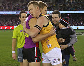 Nick Riewoldt of the Saints and Jack Riewoldt of the Tigers hug hands after the coin toss during the round 16 AFL match between the St Kilda Saints...