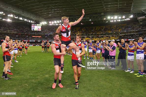 Nick Riewoldt of the Saints gets carried off after his 300th match by Sam Fisher of the Saints and Sean Dempster during the match between the StKilda...