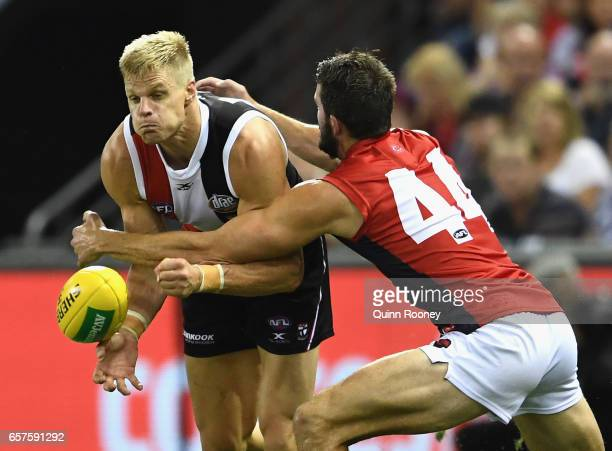Nick Riewoldt of the Saints handballs whilst being tackled Joel Smith of the Demons during the round one AFL match between the St Kilda Saints and...