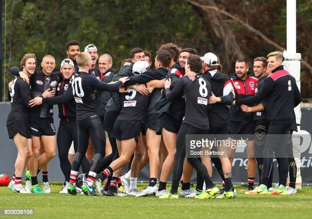 Nick Riewoldt of the Saints Jarryn Geary of the Saints and their teammates embrace during a training exercise during a St Kilda Saints AFL training...