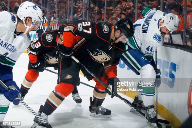 Nick Ritchie of the Anaheim Ducks battles for the puck against Erik Gudbranson and Markus Granlund of the Vancouver Canucks during the game on...