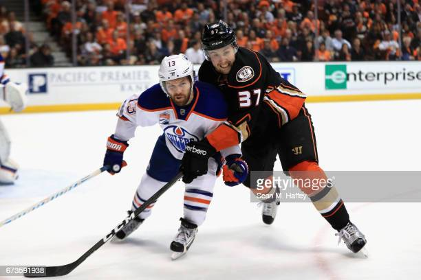 Nick Ritchie of the Anaheim Ducks battles with David Desharnais of the Edmonton Oilers for a loose puck in the first period in Game One of the...