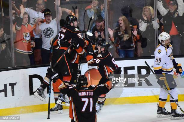 Nick Ritchie of the Anaheim Ducks jumps into the arms of teammate Ryan Getzlaf while Brandon Montour and Ondrej Kase join the celebration as Roman...