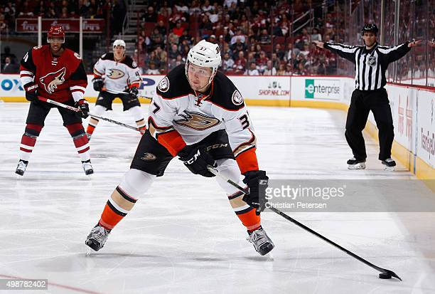 Nick Ritchie of the Anaheim Ducks skates in with the puck ahead of Anthony Duclair of the Arizona Coyotes during the third period of the NHL game at...