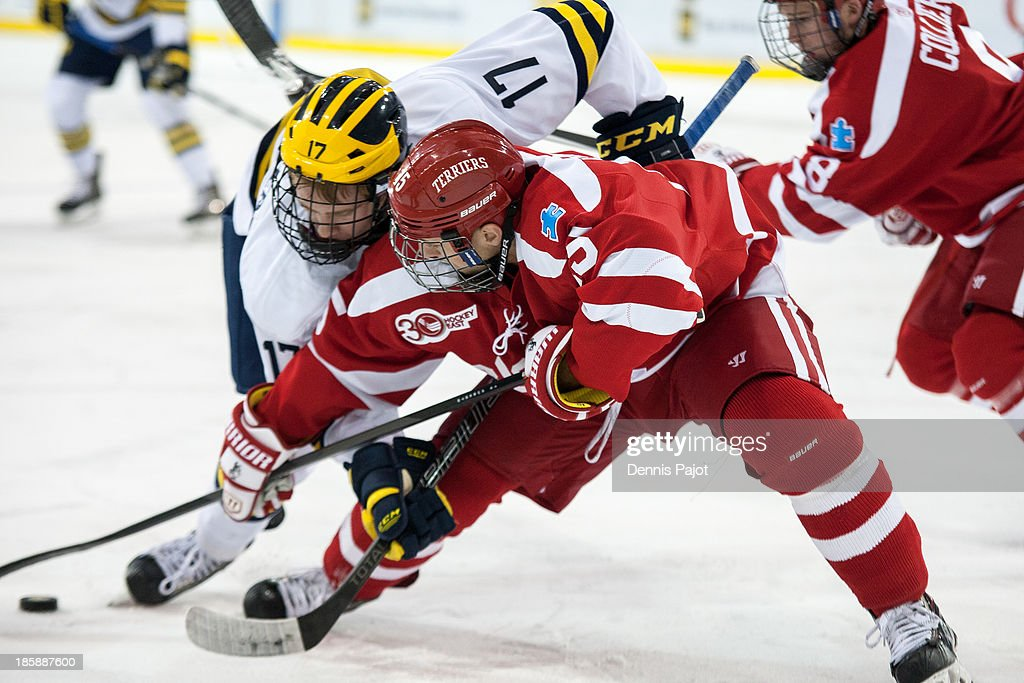 Nick Roberto #15 of the Boston University Terriers battles against JT Compher #17 of the Michigan Wolverines on October 25, 2013 at Yost Ice Arena in Ann Arbor, Michigan.