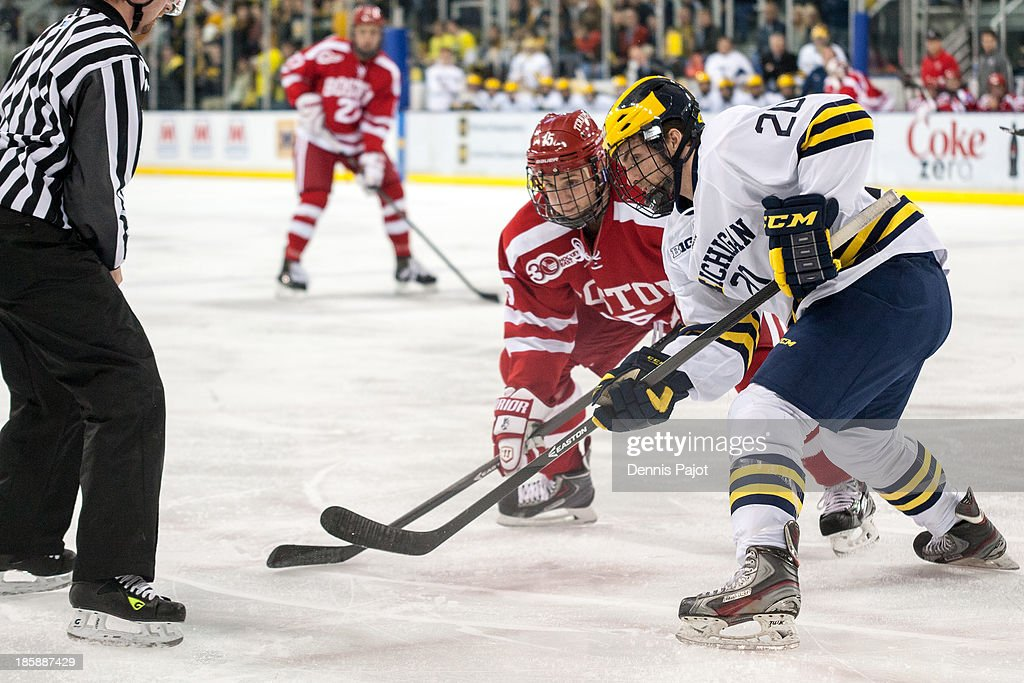 Nick Roberto #15 of the Boston University Terriers faces off against Travis Lynch #20 of the Michigan Wolverines on October 25, 2013 at Yost Ice Arena in Ann Arbor, Michigan.