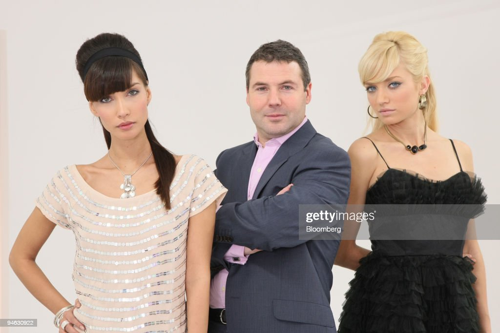 Nick Robertson chief executive officer of internet fashion retailer Asos Plc poses with models Mariel Booth and Elodie Bonis in London UK on Tuesday...