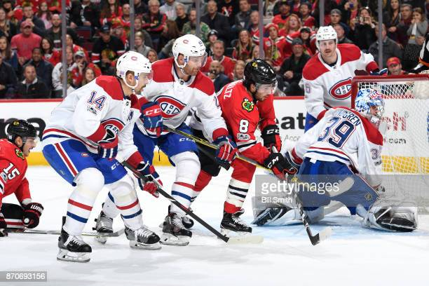 Nick Schmaltz of the Chicago Blackhawks watches for the puck next to Tomas Plekanec and Karl Alzner of the Montreal Canadiens in the third period at...