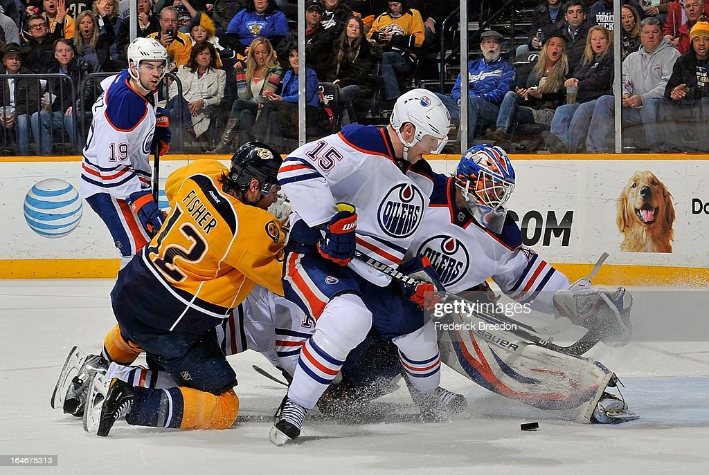 Nick Schultz #15 of the Edmonton Oilers and Mike Fisher #12 of the Nashville Predators get tied up in front of Oilers goalie Devan Dubnyk #40 at the Bridgestone Arena on March 25, 2013 in Nashville, Tennessee.