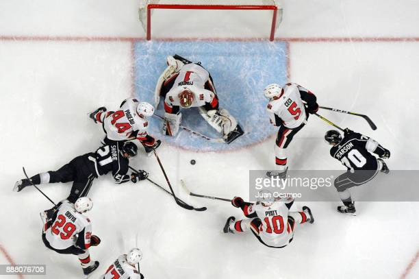 Nick Shore of the Los Angeles Kings battles for the puck against JeanGabriel Pageau Mike Condon and Tom Pyatt of the Ottawa Senators at STAPLES...