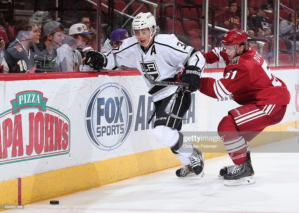 Nick Shore #37 of the Los Angeles Kings skates with the puck ahead of Christian Dvorak #51 of the Arizona Coyotes during the NHL rookie camp game at Gila River Arena on September 16, 2014 in Glendale, Arizona.