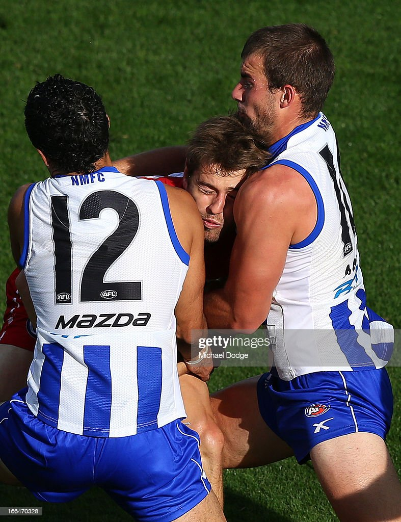 Nick Smith of the Swans gets tackled by Lindsay Thomas (L) and Ben Cunnington of the Kangaroos during the round three AFL match between the North Melbourne Kangaroos and the Sydney Swans at Blundstone Arena on April 13, 2013 in Hobart, Australia.