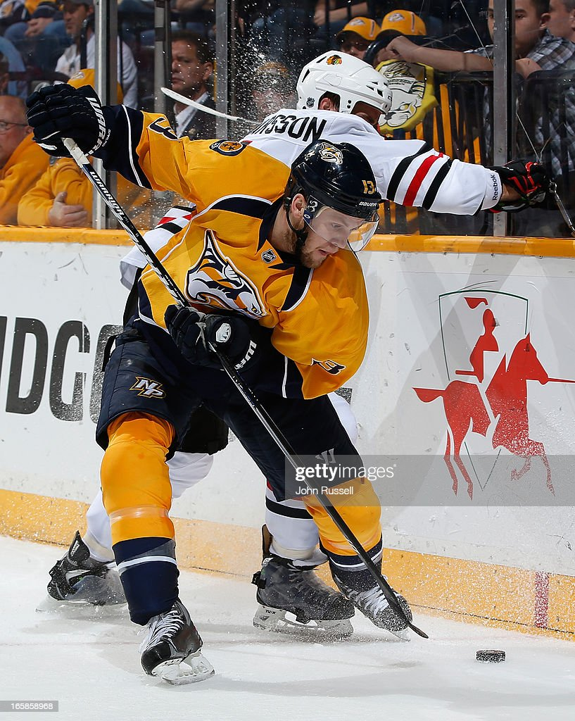 Nick Spaling #13 of the Nashville Predators battles along the boards against Niklas Hjalmarsson #4 of the Chicago Blackhawks during an NHL game at the Bridgestone Arena on April 6, 2013 in Nashville, Tennessee.