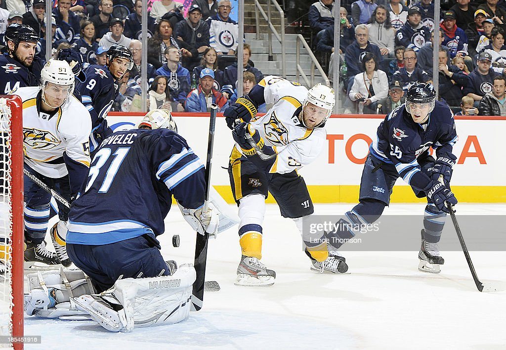 <a gi-track='captionPersonalityLinkClicked' href=/galleries/search?phrase=Nick+Spaling&family=editorial&specificpeople=4112920 ng-click='$event.stopPropagation()'>Nick Spaling</a> #13 of the Nashville Predators takes a shot on net as goaltender Ondrej Pavelec #31 of the Winnipeg Jets butterflies in the crease to make a save during third period action at the MTS Centre on October 20, 2013 in Winnipeg, Manitoba, Canada.