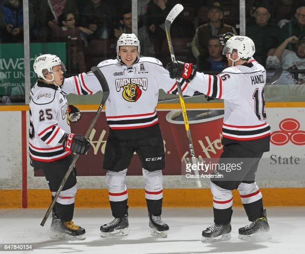 Nick Suzuki of the Owen Sound Attack celebrates a goal with teammates Petrus Palmu and Kevin Hancock against the Peterborough Petes during an OHL...