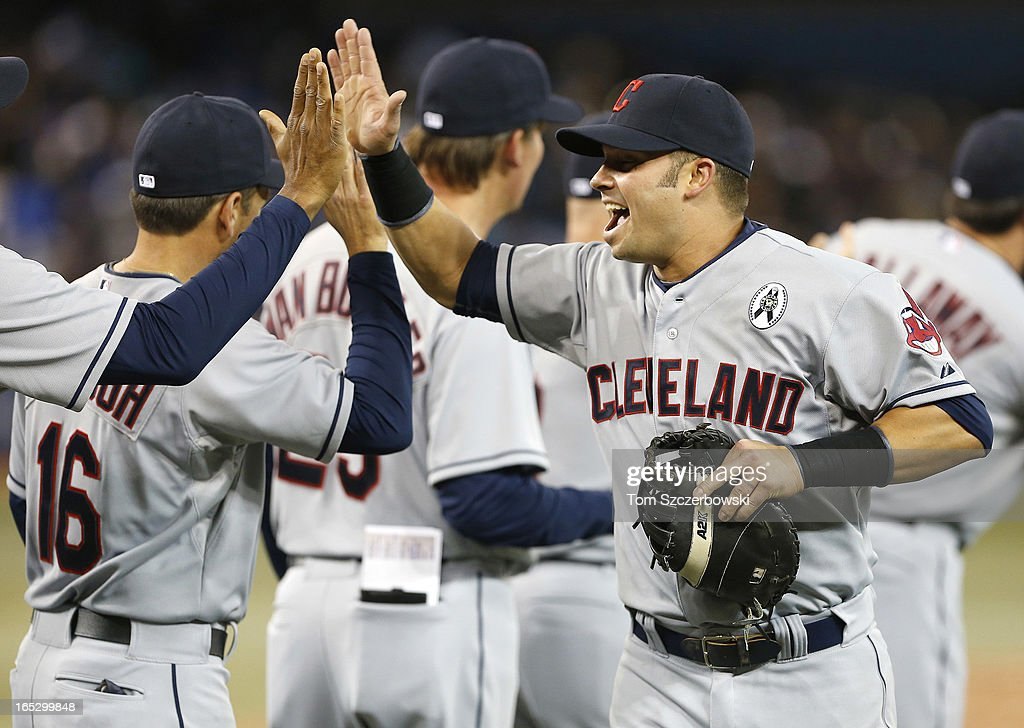 <a gi-track='captionPersonalityLinkClicked' href=/galleries/search?phrase=Nick+Swisher&family=editorial&specificpeople=206417 ng-click='$event.stopPropagation()'>Nick Swisher</a> #33 of the Cleveland Indians celebrates with teammates during MLB game action on Opening Day after defeating the Toronto Blue Jays on April 2, 2013 at Rogers Centre in Toronto, Ontario, Canada.