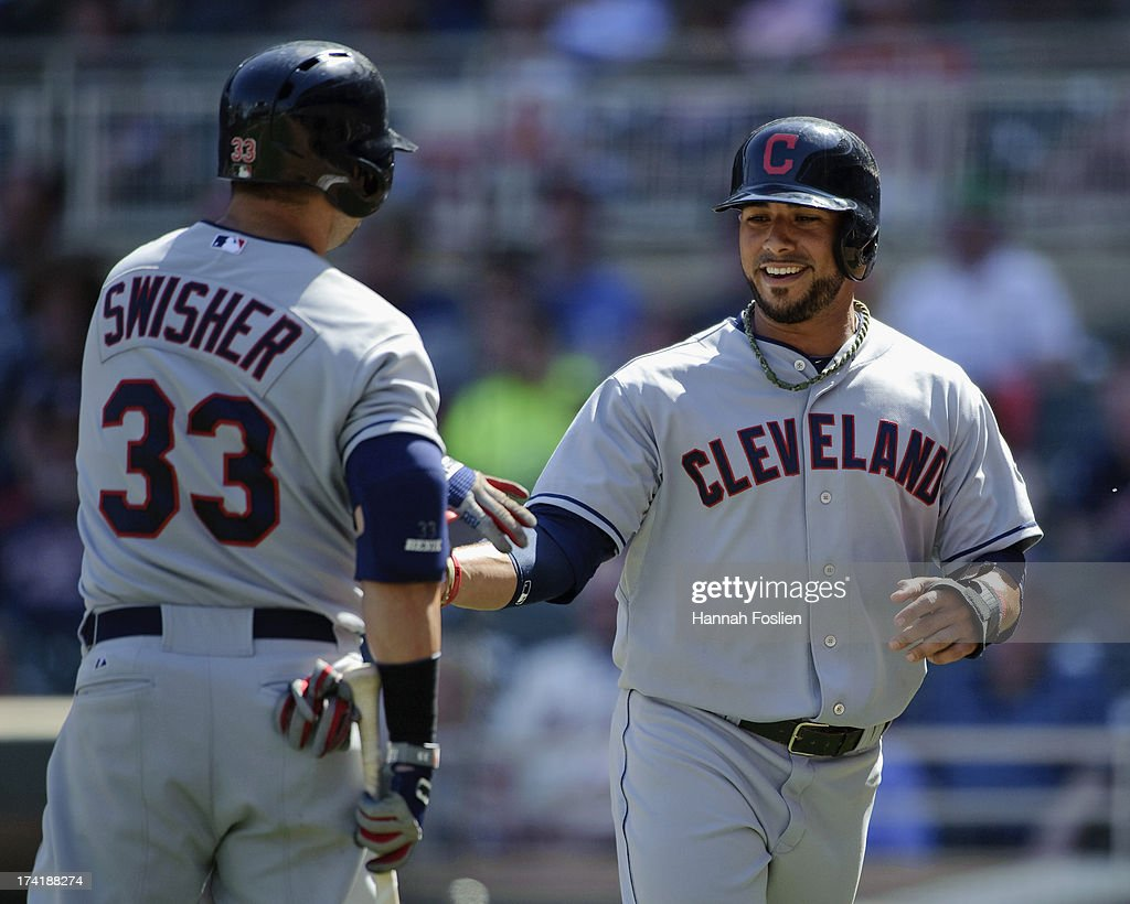 Nick Swisher #33 of the Cleveland Indians congratulates teammate Mike Aviles #4 on scoring a run against the Minnesota Twins during the ninth inning of the game on July 21, 2013 at Target Field in Minneapolis, Minnesota. The Indians defeated the Twins 7-1.