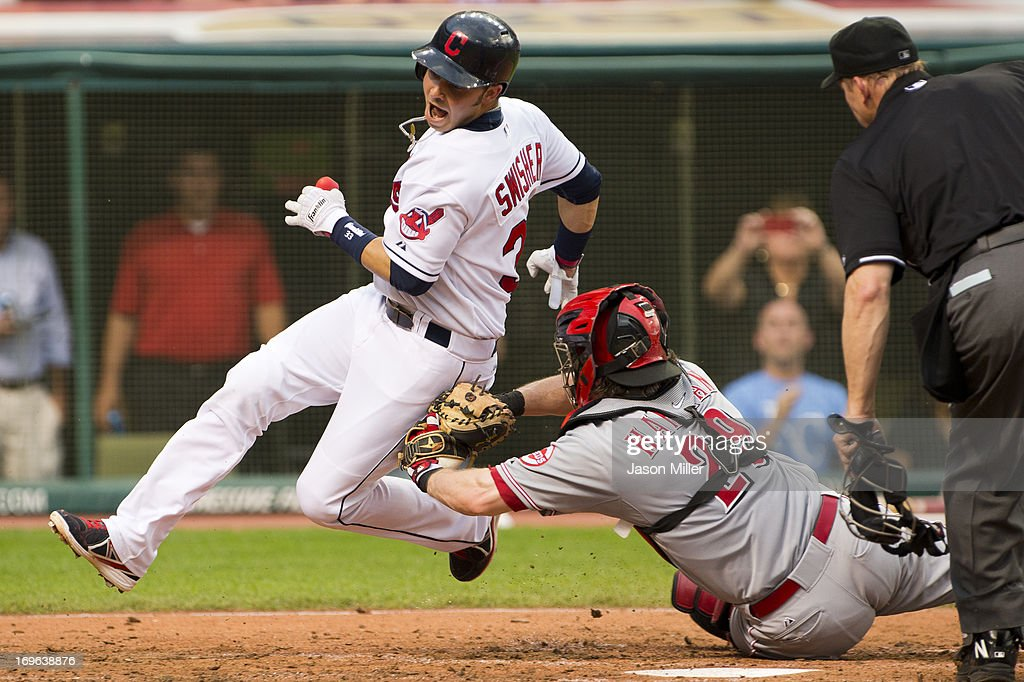 Nick Swisher of the Cleveland Indians tries to score off a double by Jason Giambi but is tagged out by catcher Ryan Hanigan of the Cincinnati Reds...