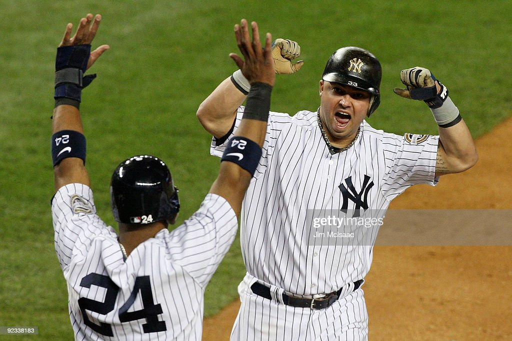 Nick Swisher of the New York Yankees and Robinson Cano celebrate scoring off a single by Johnny Damon in the bottom of the fourth inning against the...