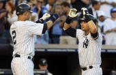 Nick Swisher of the New York Yankees celebrates his first inning two run home run against the Toronto Blue Jays with teammate Derek Jeter on August 2...