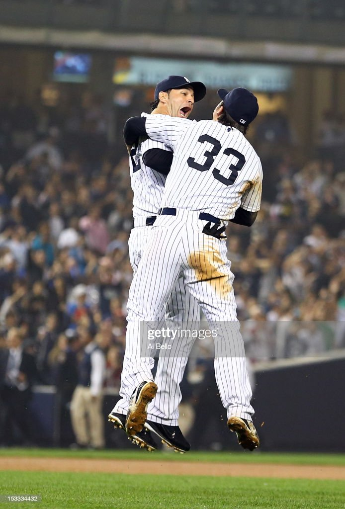 Nick Swisher #33 of the New York Yankees celebrates the win over the Boston Red Sox with teammate Eric Chavez #12 on October 3, 2012 at Yankee Stadium in the Bronx borough of New York City. With the win, the New York Yankees clinch the A.L. East Division title.